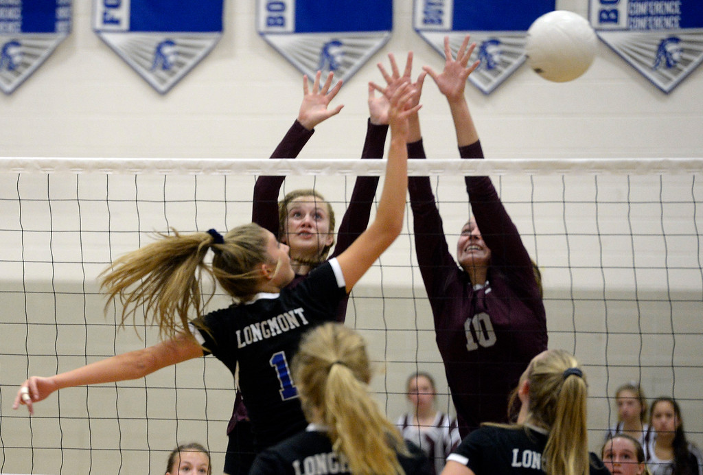 . LONGMONT, CO: September 18: Longmont\'s Caroline Demosthenes trie to hit past Silver Creek\'s Kaitlin James and Caitlin Volksmann. Silver Creek played Longmont at LHS on September 18, 2018.  (photo by Cliff Grassmick/Staff Photographer).