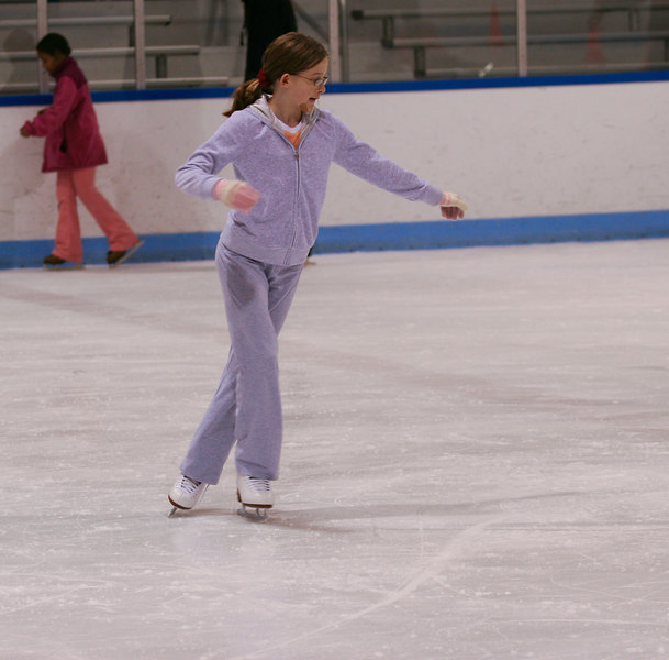 The young skater does a backward crossover.