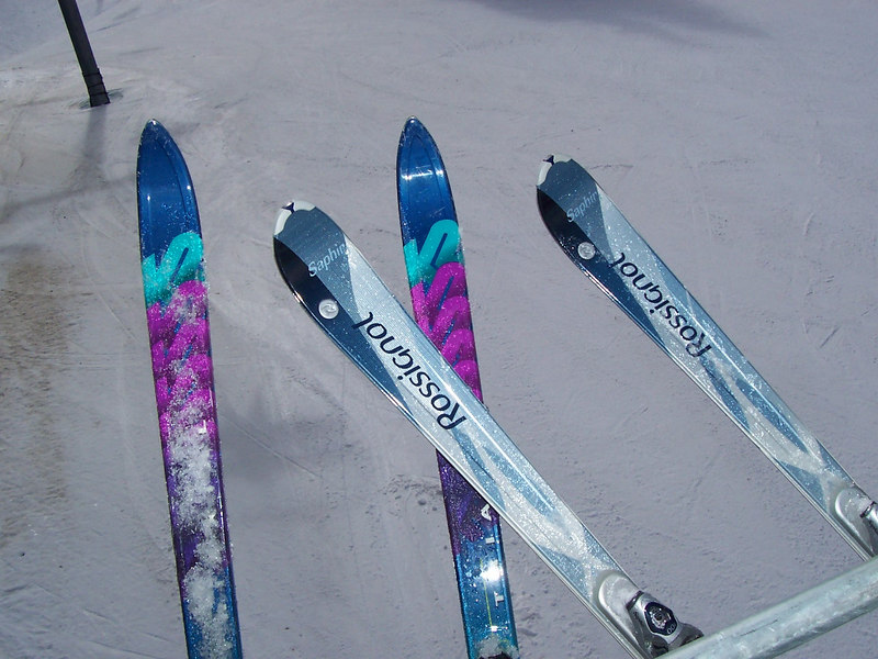 "Chris' skis on the left are the old style straight skis. Caroline has the newer style parabolic or ""shaped"" skis with wide tips and tails but a narrow middle. This picture was taken on the lift at Taos."
