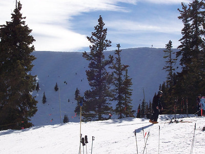 Skiers prepare to ski from the top of Tos Mountain.