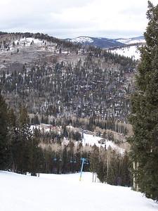 Looking down a slope at the lodge and parking lot at Pajarito.