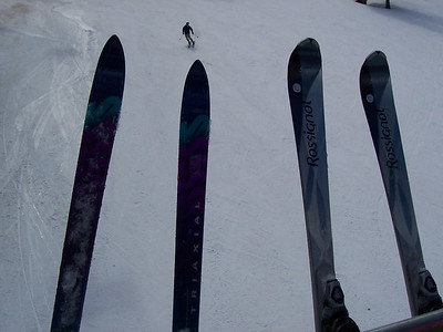 """Chris' skis on the left are the old style straight skis. Caroline has the newer style parabolic or """"shaped"""" skis with wide tips and tails but a narrow middle. This picture was taken on the lift at Taos."""