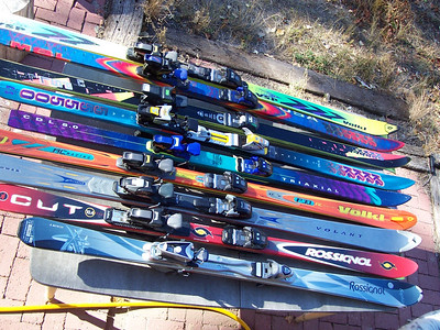 """The blue and purple skis in the middle were Chris's skis last season. The silver Rossignol's at the bottom were Caroline's. Chris got the red Rossignol skis a few months ago as his new primary skis, but after picking up FIVE more pairs of skis at the Santa Fe ski swap for $20 we'll both be able to try out a bunch of different skis! Actually, most of the top five """"straght: skis will be used in place of wood slats to build a ski-themed bench to sit on."""