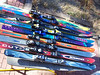 "The blue and purple skis in the middle were Chris's skis last season. The silver Rossignol's at the bottom were Caroline's. Chris got the red Rossignol skis a few months ago as his new primary skis, but after picking up FIVE more pairs of skis at the Santa Fe ski swap for $20 we'll both be able to try out a bunch of different skis! Actually, most of the top five ""straght: skis will be used in place of wood slats to build a ski-themed bench to sit on."