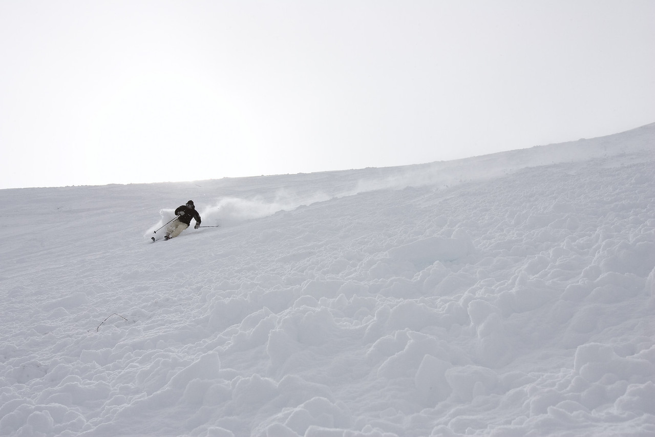 The skier has completed a left hand turn and is initiating a linked turn to the right by reaching out with his downhill (right) pole. Notice the upper body is facing downhill and the downhill reach with the downhill pole will square the upper body to the fall line.