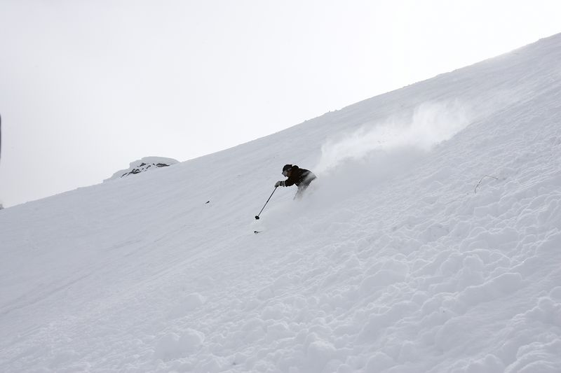 The skier completes the turn by transfering his weight slightly to his left ski and rocking his weight slightly from toe to heel, allowing the shape of the ski to carve the bottom part of the turn. He is now reaching out his left and and pole to initiate the next turn.