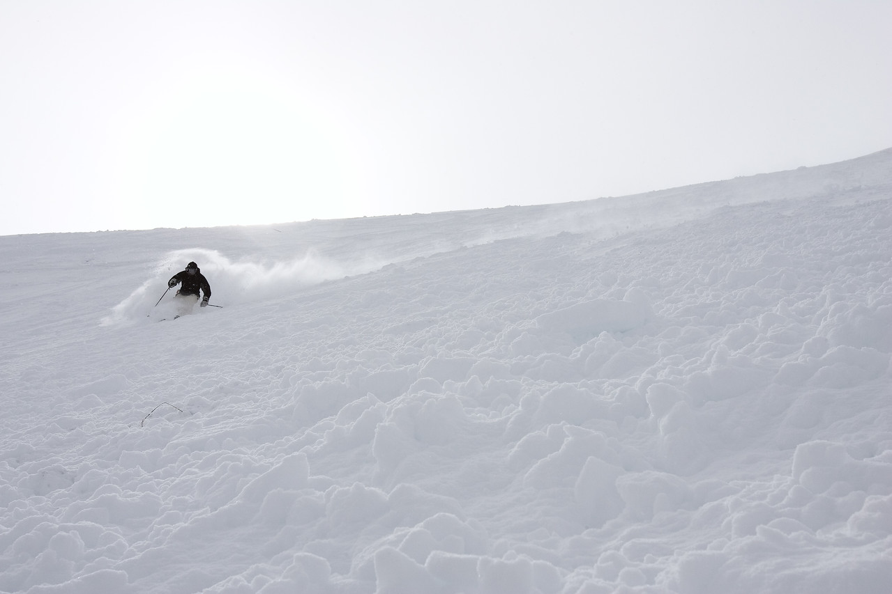 The pole plant is complete and now the skier drives his knees downhill, flattening his edges and allowing them to glide naturally into the fall line. Meanwhile, he is bringing his left hand and pole forward to be ready to initiate the next turn.