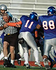 Referee Mike Shumway gets caught up in the mix at a semipro football game between the Snohomish County Vikings and Oregon Thunderbolts on 8/6/2006.