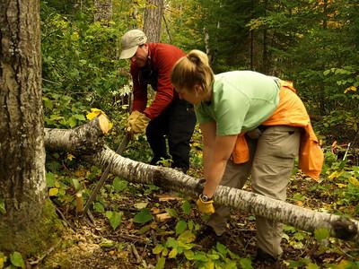 "Joe and Eva hard at work.  Eva is lifting the log to prevent ""binding."""