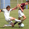 #26 for Sullivan South slides in and kicks the ball away from #11 of Knox Bearden. Photo by Ned Jilton II