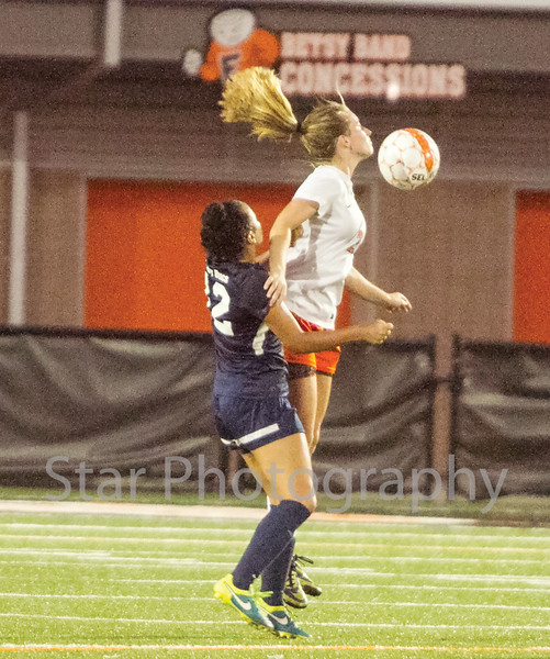Star Photo/Larry N. Souders<br /> A University High defender challenges Elizabethton's (20) on a header.