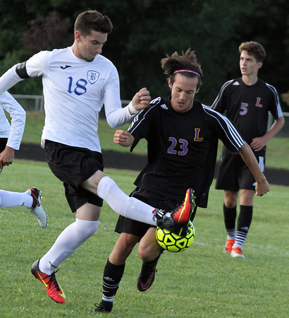 Record-Eagle/James Cook Buckley's Garrett Luther (18) tries to keep the ball away from Leland's Max Morgan (23) in Wednesday's soccer game at Buckley. Leland won 1-0 in a shootout.