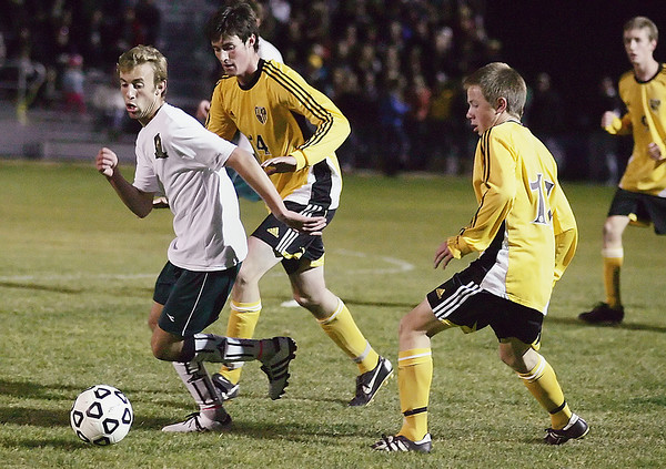 Record-Eagle/Keith King<br /> Traverse City West's Mitch Taplin is pressured by Traverse City Central's Kevin Trippe, middle, and Matt Westerman, right, Tuesday, October 19, 2010 at Traverse City West High School.