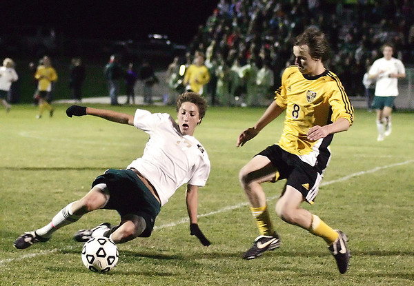 Record-Eagle/Keith King<br /> Traverse City West's Kevin Cronin slides to kick the ball away from Traverse City Central's Bennett Weckler Tuesday, October 19, 2010 at Traverse City West High School.