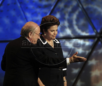 FIFA President Sepp Blatter, left, passes over the spotlight to Brazilian President Dilma Rousseff at the Preliminary Draw of the 2014 FIFA World Cup Brazil in Rio de Janeiro, Brazil, July 30, 2011. The 2014 World Cup took shape Saturday as the qualifying draw laid out each nation's path to securing a spot in the tournament in three years' time. The draw determined the layout of the qualifying groups for Africa; North, Central America and the Caribbean; Asia; Europe; and Oceania. (Austral Foto/Renzo Gostoli)