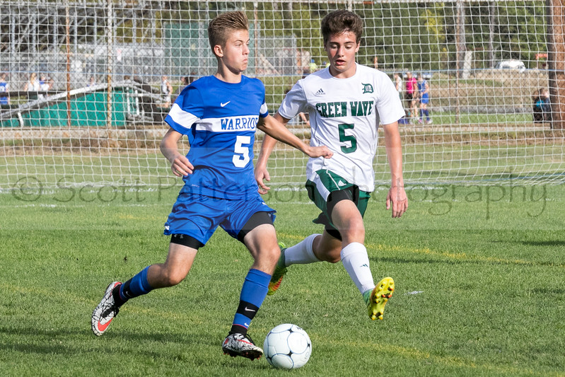 Winnacunnet's Drew Forsley prepares to pass the ball as Dover's Evan Dodier gives chase during Division I Varsity Boys Soccer in Dover on Tuesday. Photo by Scott Patterson/Fosters.com