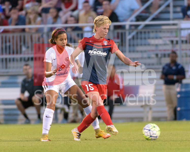 Midfielder Joanna Lohman pass the ball off after disposessing it from Frances Silva.