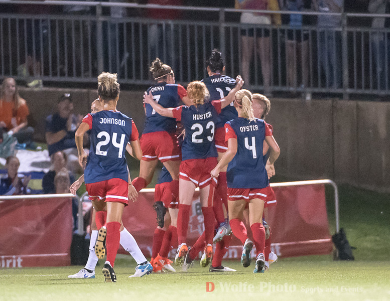 Washington Spirit forward, Katie Stegal scored a goal and gets swarmed by the rest of the on-field Spirit team.  She is buried under congratulatory gestures.
