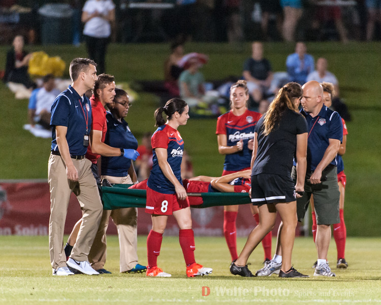 Supported by her team mates, Ca;i is carried off the pitch.
