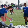 Kaleigh Riehl (3) on  the right scoops up the game ball out of a snow pile as  Ellie Jean (14) catches her breath.