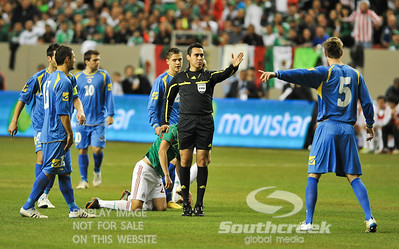Referee Jair Marrufo signals the call while Bosnia-Herzegovina's Defender Adnan Mravac (#5) protests during Soccer action between Bosnia-Herzegovina and Mexico.  Mexico defeated Bosnia-Herzegovina 2-0 in the game at the Georgia Dome in Atlanta, GA.