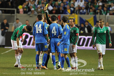 Referee Jair Marrufo gives a yellow card as Bosnia-Herzegovina's Forward Vedad Ibisevic (#14) and Bosnia-Herzegovina's Defencer Emir Spahic (#4) argue their case during Soccer action between Bosnia-Herzegovina and Mexico.  Mexico defeated Bosnia-Herzegovina 2-0 in the game at the Georgia Dome in Atlanta, GA.