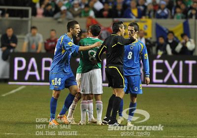 Referee Jair Marrufo tries to make the call as Bosnia-Herzegovina's Forward Vedad Ibisevic (#14) and Bosnia-Herzegovina's Midfielder Miralem Pjanic (#8) protest during Soccer action between Bosnia-Herzegovina and Mexico.  Mexico defeated Bosnia-Herzegovina 2-0 in the game at the Georgia Dome in Atlanta, GA.
