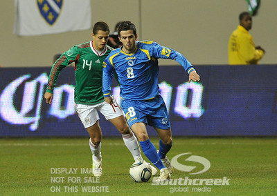 Bosnia-Herzegovina's Midfielder Miralem Pjanic (#8) attempts to get away from Mexico's Forward Javier Hernandez (#14) during Soccer action between Bosnia-Herzegovina and Mexico.  Mexico defeated Bosnia-Herzegovina 2-0 in the game at the Georgia Dome in Atlanta, GA.