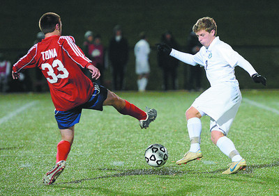 Lewisburg Green Dragons' Broson Ferster keeps the ball away from Coughlin Crusaders' Joey Tona during the Class AA state playoff game in Loyalsock on Tuesday night.