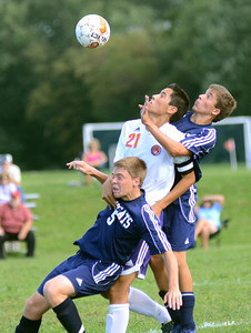 Danville's Andrew Smith collides with Mifflinburg's Brandon Lee, left, and Trent Miller while going for a free ball during their game Wednesday Sept. 5, 2012 in Danville.