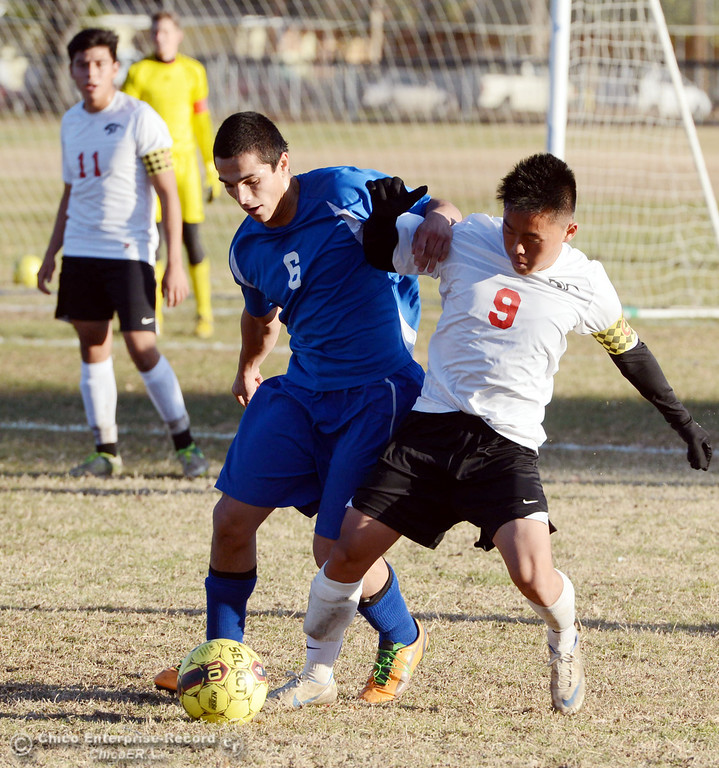. Chico High\'s #9 Rocky Xiong (right) battles against Orland High\'s #6 Hector Gutierrez (left) in the first half of their boys soccer game at CHS Thursday, December 19, 2013 in Chico, Calif. (Jason Halley/Chico Enterprise-Record)
