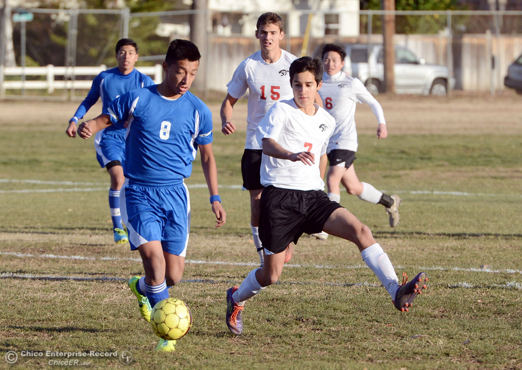 . Orland High\'s #8 Israel Zintzun (left) against Chico High\'s #7 Claudio Quezada (right) in the first half of their boys soccer game at CHS Thursday, December 19, 2013 in Chico, Calif. (Jason Halley/Chico Enterprise-Record)