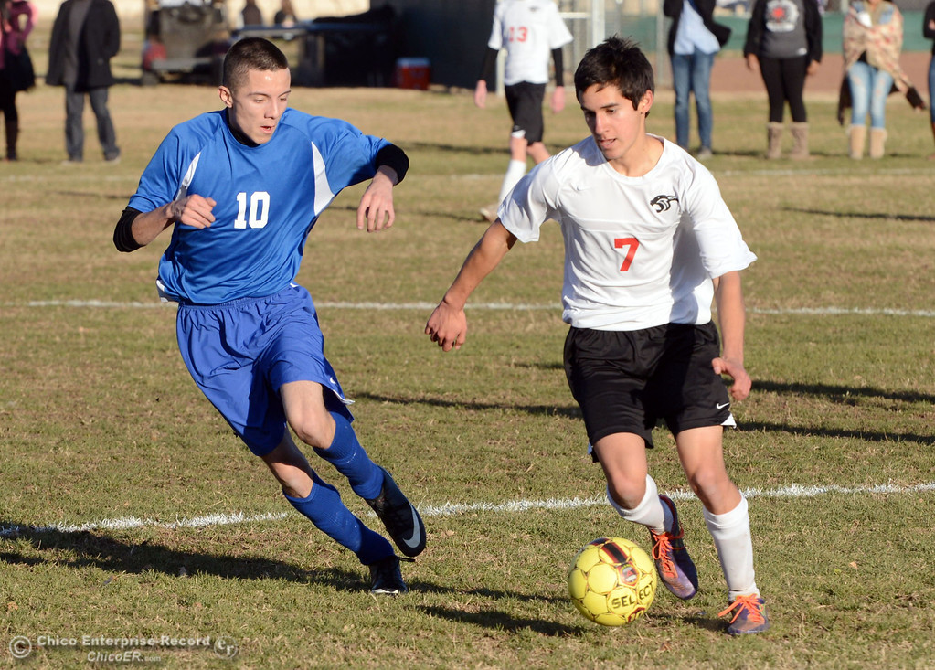 . Chico High\'s #7 Claudio Quezada (right) battles against Orland High\'s #10 Marcos Martinez (left) in the first half of their boys soccer game at CHS Thursday, December 19, 2013 in Chico, Calif. (Jason Halley/Chico Enterprise-Record)