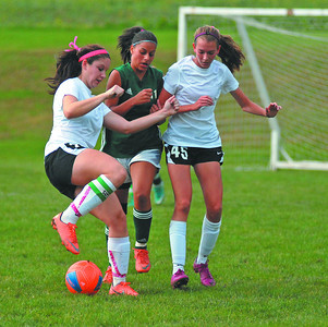 Meadowbrook Christian Academy's Madison Burrows and Adrienne Yordy fight for possession of the ball with Sunbury Christian Academy's Sarah Spangler during the soccer game in Milton on Tuesday afternoon.