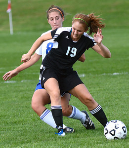 Southern Columbia's Erin Yoder stays between Warrior Run's Sophie Biddle and the ball during their game Tuesday Sept. 11, 2012.
