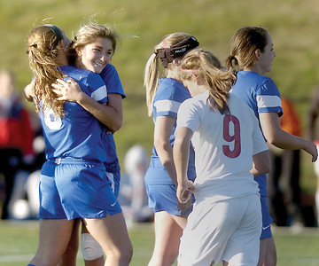 Warrior Run's Olivia George and Madison Bennett hug after Tuesday's victory against Selinsgrove in the D4 soccer playoffs at Loyalsock High School.