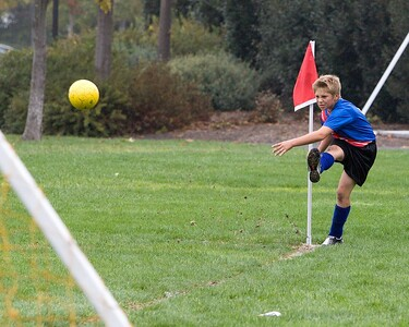Dirt flies along with the ball from Miles' corner kick.