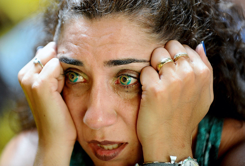 . Wearing Brazilian flag contact lenses, Brazilian soccer fan Elizangela Santos, of Clinton, Mass., reacts after watching television coverage of Brazil\'s loss to Belgium in a World Cup soccer quarterfinal, Friday, July 6, 2018, in Framingham, Mass. (Ken McGagh/The Metro West Daily News via AP)