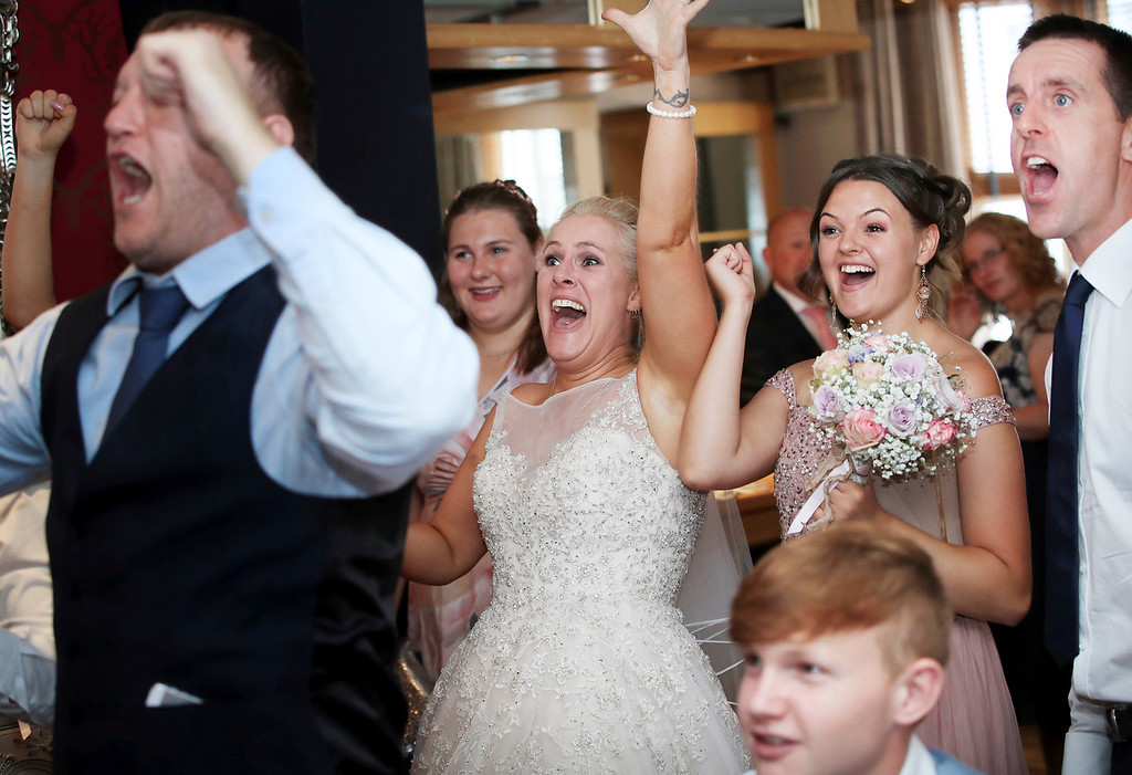 . Soccer fan bride Nadine Hanlon, centre reacts after England scored, whilst watching the quarterfinal match between Sweden and England at the 2018 soccer World Cup on a television, at the Regent Hotel, in Doncaster, England, Saturday July 7, 2018. The bride and her groom Lee Hanlon watched the game with their guests prior to their wedding breakfast. (Danny Lawson/PA Wire/PA via AP)