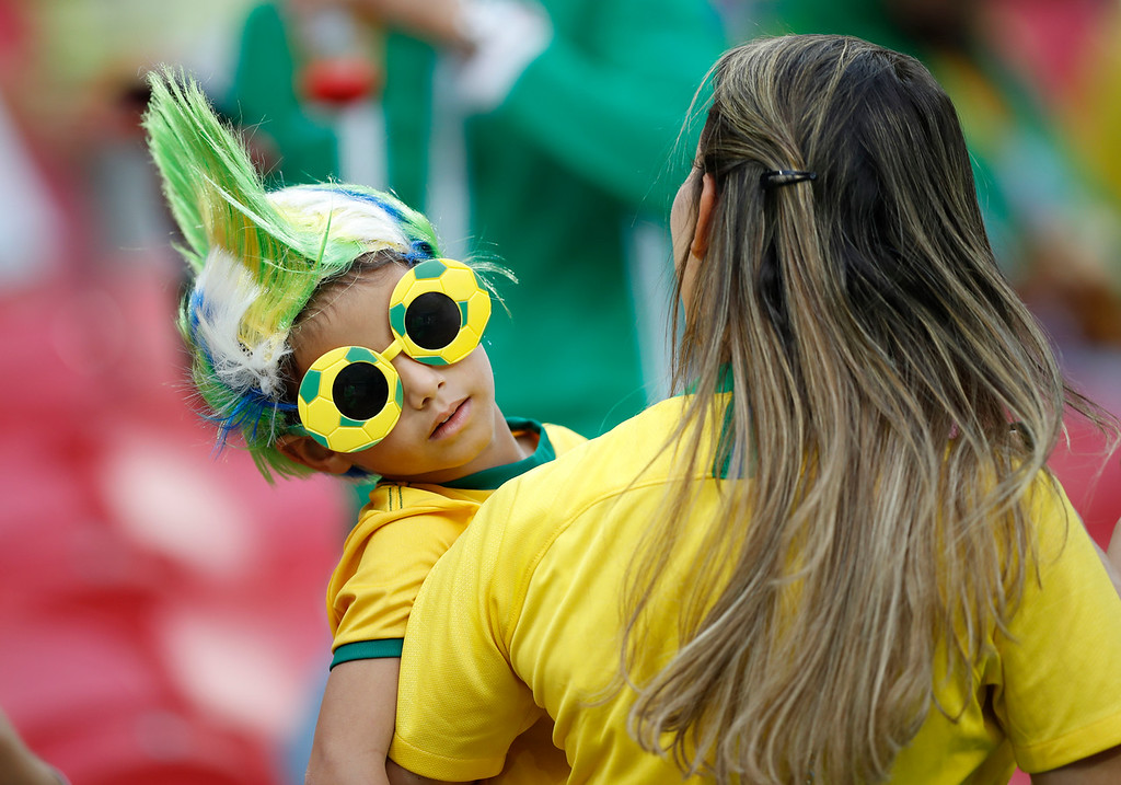 . A woman carries a young Brazil fan prior to the quarterfinal match between Brazil and Belgium at the 2018 soccer World Cup in the Kazan Arena, in Kazan, Russia, Friday, July 6, 2018. (AP Photo/Francisco Seco)