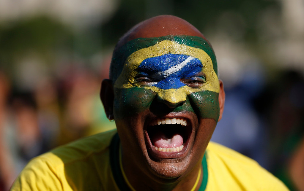. A Brazil soccer fan cheers for his team prior a live telecast of the Brazil vs. Belgium World Cup quarter finals soccer match, in Rio de Janeiro, Brazil, Friday, July 6, 2018. (AP Photo/Silvia Izquierdo)