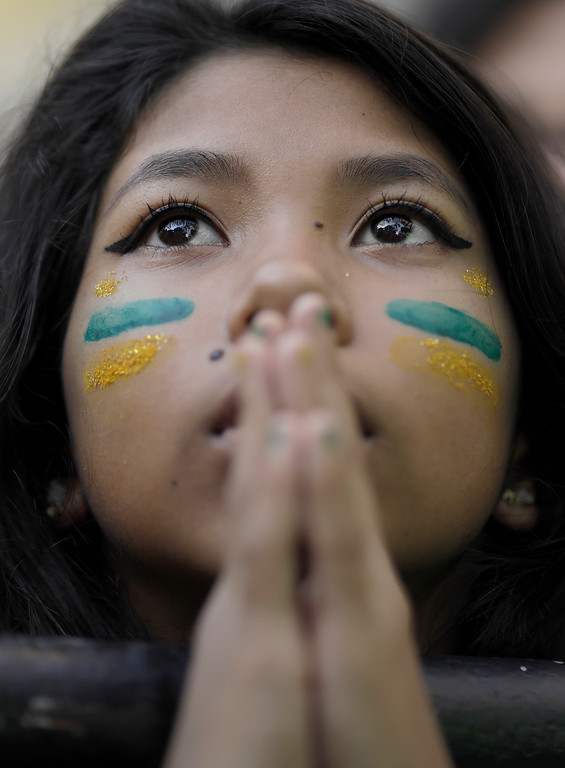. A Brazil soccer fan watches a live broadcast of the Russia World Cup quarterfinal match between Brazil and Belgium in Rio de Janeiro, Brazil, Friday, July 6, 2018. Belgium knocked Brazil out of the World Cup and advanced to the semi-finals. (AP Photo/Leo Correa)