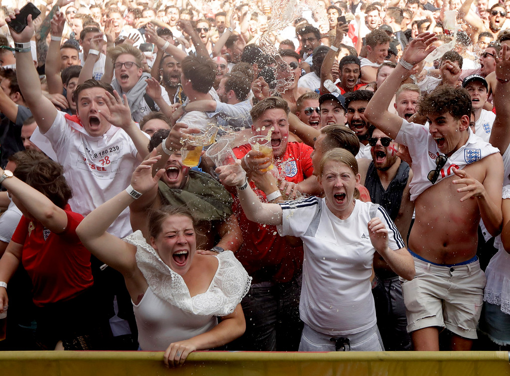. England soccer fans celebrate their second goal as they watch a live broadcast on a big screen showing the quarterfinal match between England and Sweden at the 2018 soccer World Cup, in Flat Iron Square, south London, Saturday, July 7, 2018. (AP Photo/Matt Dunham)