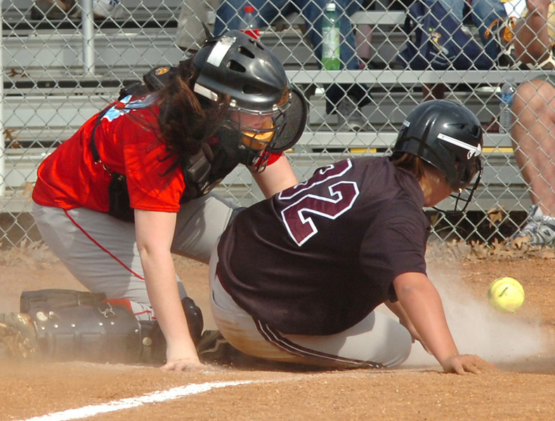 South catcher, #13, and the D-B baserunner, #32, watch the ball skitter away at the plate, allowng a D-B run. Photo by Ned Jilton II