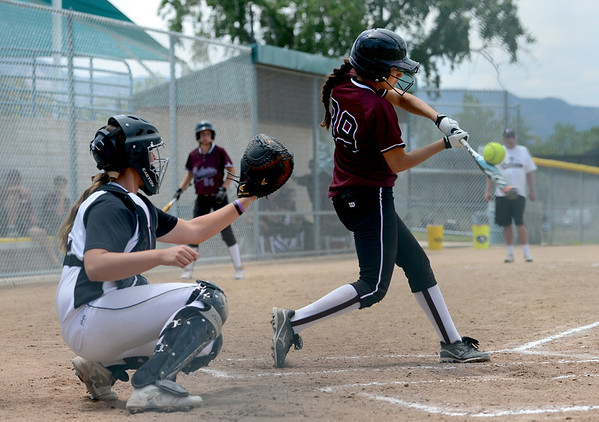 "Delaney Spaulding (99), left, of the California Batbusters, makes contact with the ball  against the SoCal Athletics in the 18-under Boulder Championship game. Rachel Sellers of the Athletics is the catcher.<br /> For more photos of the championship games, go to  <a href=""http://www.dailycamera.com"">http://www.dailycamera.com</a>.<br /> Cliff Grassmick / July 1, 2012"