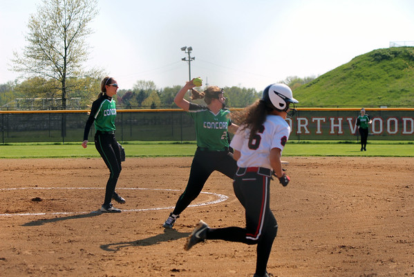 GREG KEIM | THE GOSHEN NEWS<br /> Junior first baseman Hannah Boswell of Concord throws out senior Emily Schrock of NorthWood after she executed a sacrifice bunt in an NLC softball game Thursday night at Stauffer Park in Nappanee. In the background for Concord is senior pitcher Kiley Austin.