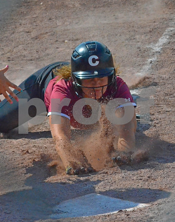 -Messenger photo by Britt Kudla<br /> Devon Carson of Clarke slide head first into home plate during Thursday's game against New Hampton