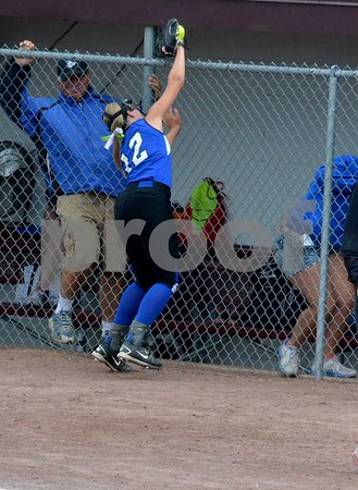 -Messenger photo by Britt Kudla<br /> Keely Bycroft of Bondurant-Farrar reaches over the fence to make the catch against Clarke on Friday