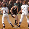 #3 for Eastside is safe at second as she runs between two Northwood players covering the base. Photo by Ned Jilton II