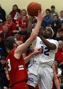 Jalen Bouldes (12), Southfield Christian, goes up for a shot over defender Wesley Bissett, Peck, during boys Class D quarterfinal basketball action at Burton Bendle High School Tuesday, March 18, 2014. (Special to the Oakland Press / LARRY McKEE)